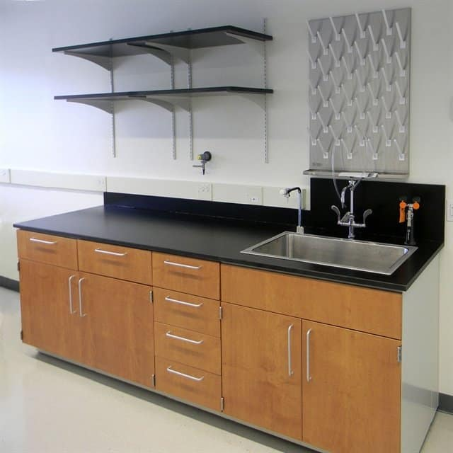 wood lab furniture with sink and drying hooks and shelves on wall