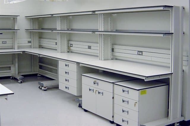 white lab furniture with undercounter storage and wall shelves.